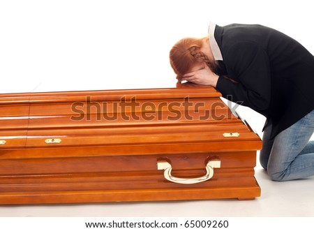 mourning - red hair young woman kneeling near coffin - stock photo