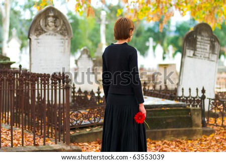 Mourning Woman at Cemetery with Red Flower - stock photo