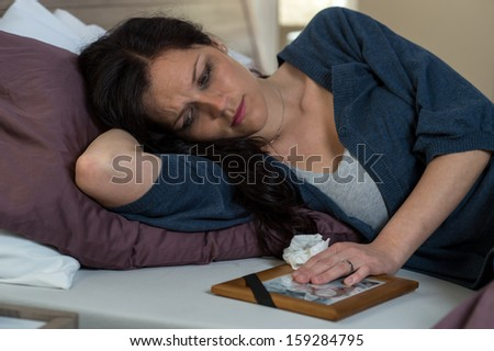 Mourning woman looking at her dead husband's photo - stock photo