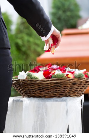 Mourning woman on funeral with flowers standing at casket or coffin - stock photo