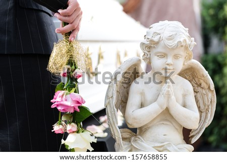 Mourning woman on funeral with pink rose standing at casket or coffin