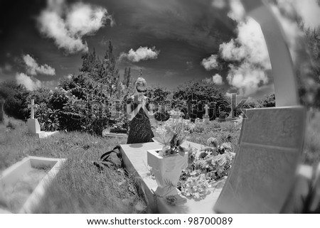 Mourning woman on her knees praying by a grave in a cemetery. Black and white, blur on borders - stock photo