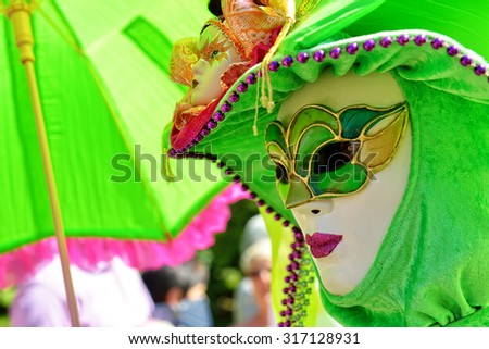 MOUSCRON, BELGIUM-JUNE 06, 2015: Participant of Venice in Mouscron promenade in Parc Communal demonstrates costume of venetian carnival - stock photo