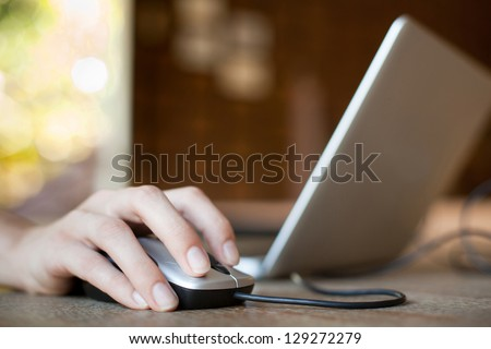 mouse click, woman hand with mouse and laptop - stock photo