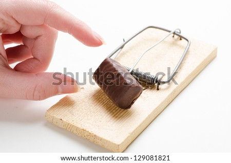 mousetrap with candy on white - stock photo
