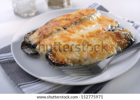 Moussaka under white sauce on a plate
