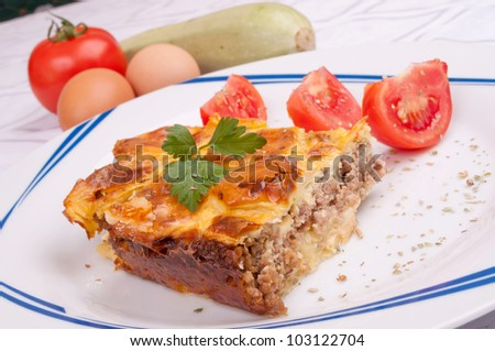 Moussaka with zucchini and minced meat and tomato salad