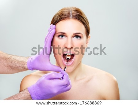 Mouth care,Close-up of female with open mouth during oral checkup at the dentist�s - stock photo