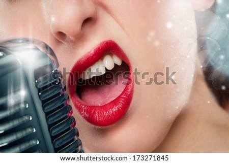 mouth of a beautiful woman singing to a microphone - stock photo