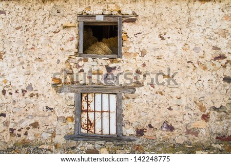 Mouth or old wooden window in barn with alpacas dry grass and straw inside. Old stone Wall revoked - stock photo
