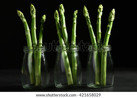 mouth-watering asparagus in jars with water on a wooden black background