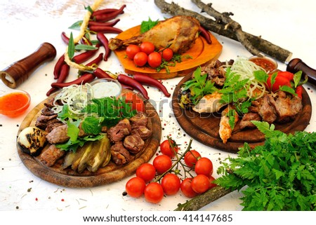 mouth-watering meat dishes grilled with vegetables on a white background