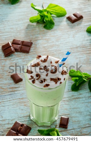 Mouthwatering mint milkshake with green apples. Popular drink for summer in America. Massive portion with pieces of chocolate and leaves of mint on the table. - stock photo