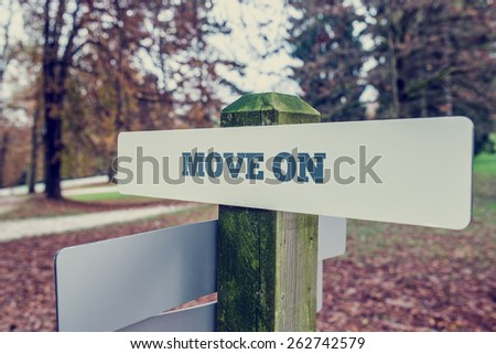 Move on concept with a rural signboard in an autumn landscape with the words - Move on - at an angled perspective. With retro effect faded look. - stock photo