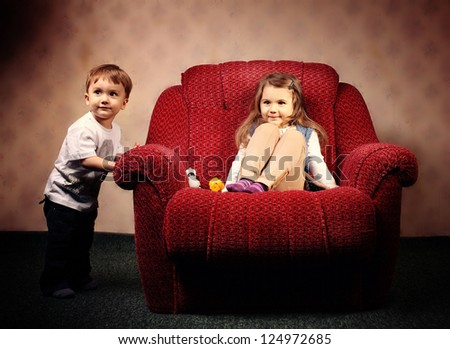move to another apartment, the children move a large red chair - stock photo