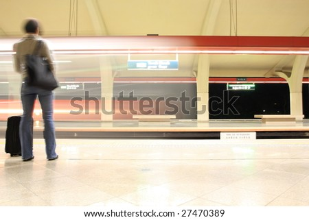 Move train on underground station with a back of commuter - stock photo
