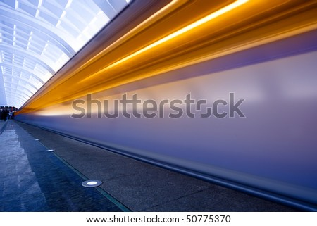 Move trains with orange lights on underground platform - stock photo