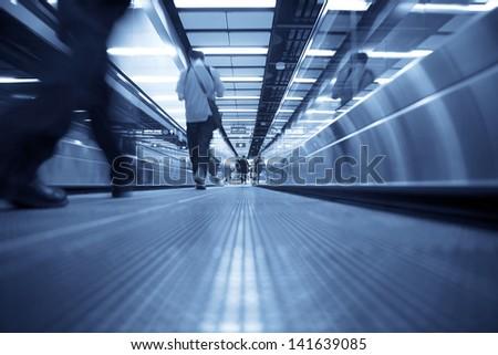 Movement of escalator with people walking - stock photo