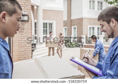 Mover holding clipboard and invoice with family in the background - stock photo