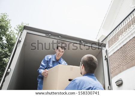 Movers unloading a moving van and passing a cardboard box - stock photo