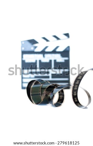 Movie clapper and 35 mm film isolated vertical frame selective focus - stock photo