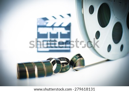 Movie clapper and 35 mm film roll on white background and selective focus - stock photo