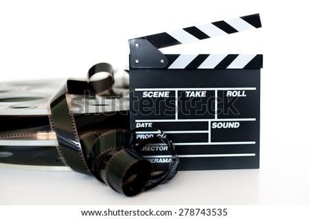 Movie clapper and vintage 35 mm film cinema reel on white background filmstrip unrolled selective focus - stock photo