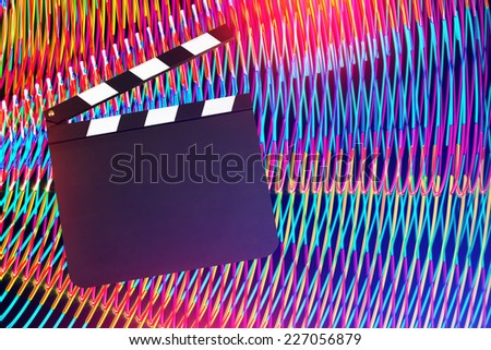 Movie clapper board against light painting background. Entertainment concept - stock photo