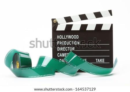 Movie clapper board and film roll over white - stock photo