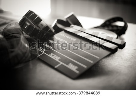 Movie clapper board and filmstrip selective focus and vintage black and white - stock photo
