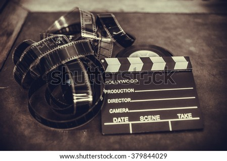 Movie clapper board and filmstrip selective focus and vintage sepia - stock photo