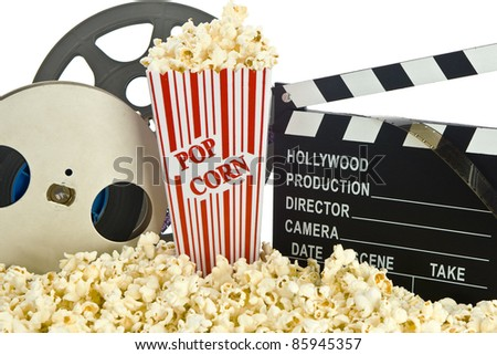 Movie Clapper Board in popcorn with film reel isolated on white