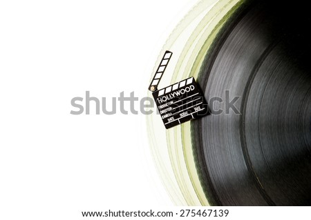 Movie clapper board on partially visible 35 mm film roll isolated on white background - stock photo