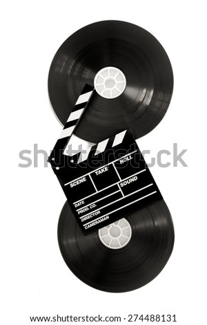 Movie clapper on 35 mm cinema film reels isolated on white background vertical frame - stock photo