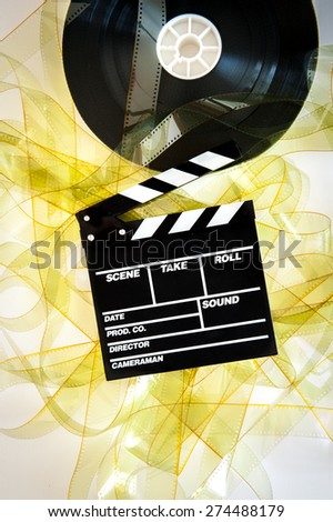 Movie clapper on 35 mm cinema reel unrolled yellow filmstrip on white background vertical - stock photo