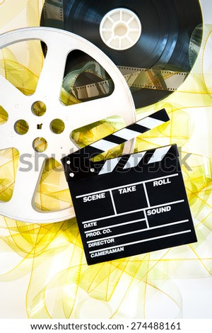 Movie clapper on 35 mm cinema reels unrolled yellow filmstrip on white background vertical - stock photo
