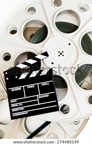 Movie clapper on two 35 mm cinema reels with film vertical frame on white background - stock photo