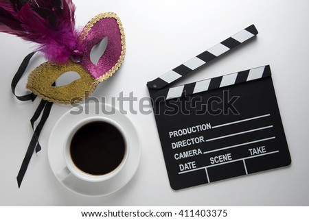 Movie clapper with a cup of coffee and carnival mask on white desk background - stock photo