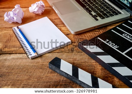 Movie clapper with notepad and pencil on wooden table - stock photo