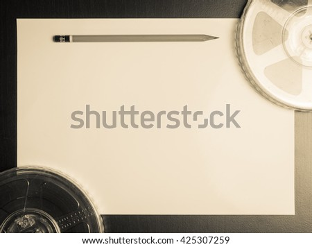 Movie film roll with pencil on paper vintage background - stock photo