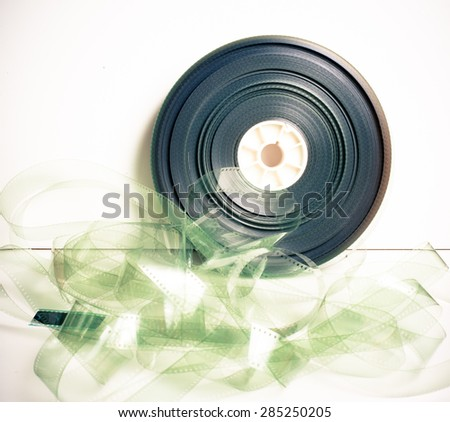 Movie 35 mm film reel on white background vintage color effect - stock photo