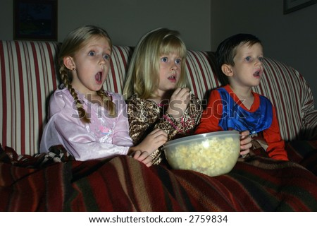 Movie Night:  Three children in their pajamas enjoy a movie in the dark while sharing a bowl of popcorn.