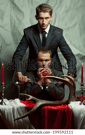 Movie poster concept. Captured a-la Hannibal Lecter criminal eating fresh heart. Policeman holding cannibal's hands with metal chain. Decadent accessories. Hollywood style. Studio shot - stock photo
