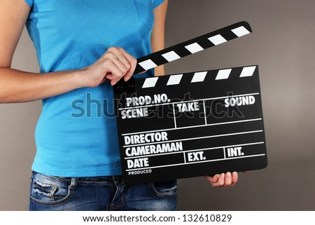 Movie production clapper board in hands on grey background - stock photo