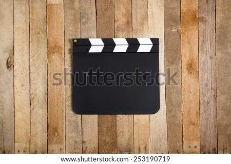 Movie production clapper board on a vintage wooden background - stock photo