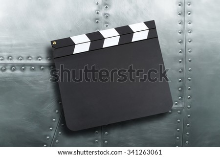 Movie production clapper board on vintage metal texture - stock photo