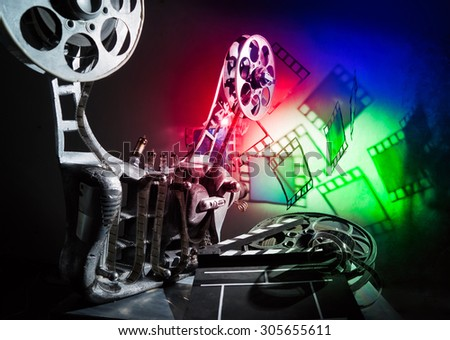 Movie projector and a film on the bright background - stock photo