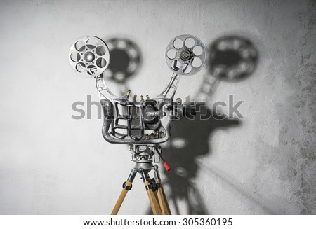 Movie projector with a film with a shadow - stock photo