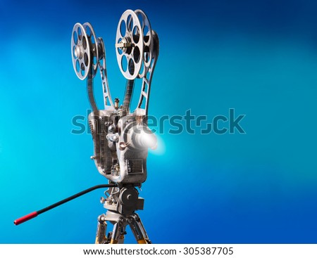 Movie projector with the film on the blue background - stock photo