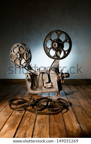 Movie projector with the film on the wooden floor - stock photo